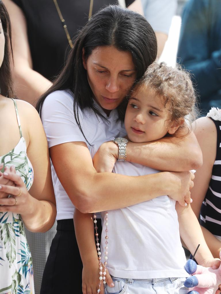 Leila clutching a child at the crash site. Picture: John Grainger