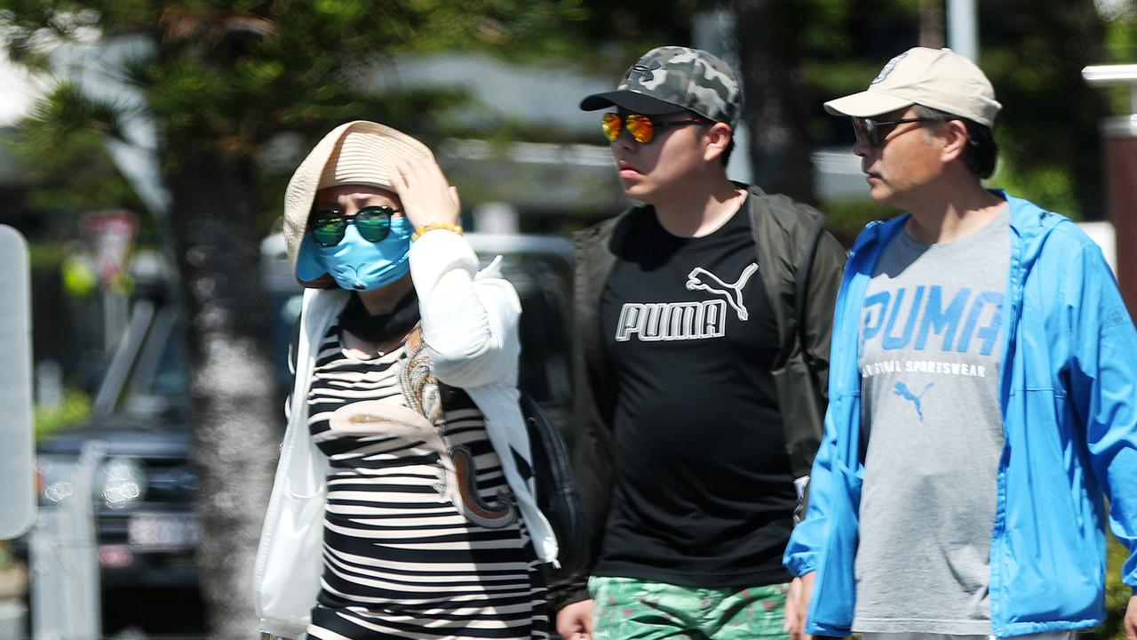 A woman wearing a mask on the Gold Coast, where nine Chinese tourists are in quarantine in the Gold Coast University Hospital, four of them testing positive to the Wuhan coronavirus. Picture: Nigel Hallett.