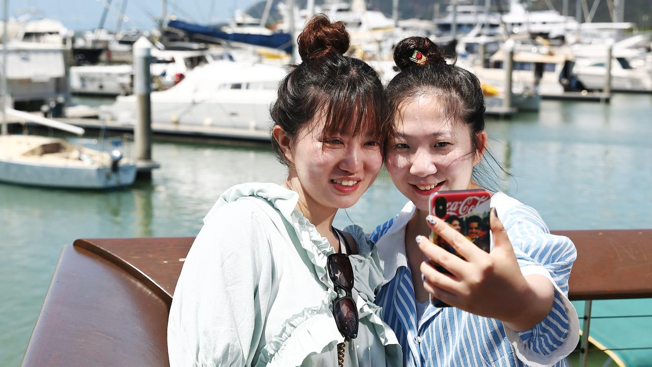 Chinese tourists Yingwen Jin and Yidie Xu take some holiday photos at the Cairns Marlin Marina, boosting tourism in Far North Queensland. PICTURE: BRENDAN RADKE