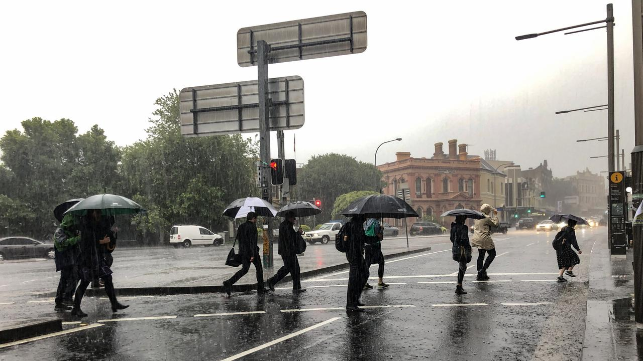 The inner city wasn't spared either with commuters struggling against rain and wind at 7am. Picture: Nicholas Eager