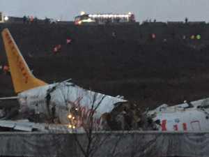 Plane skids off runway, snaps into three