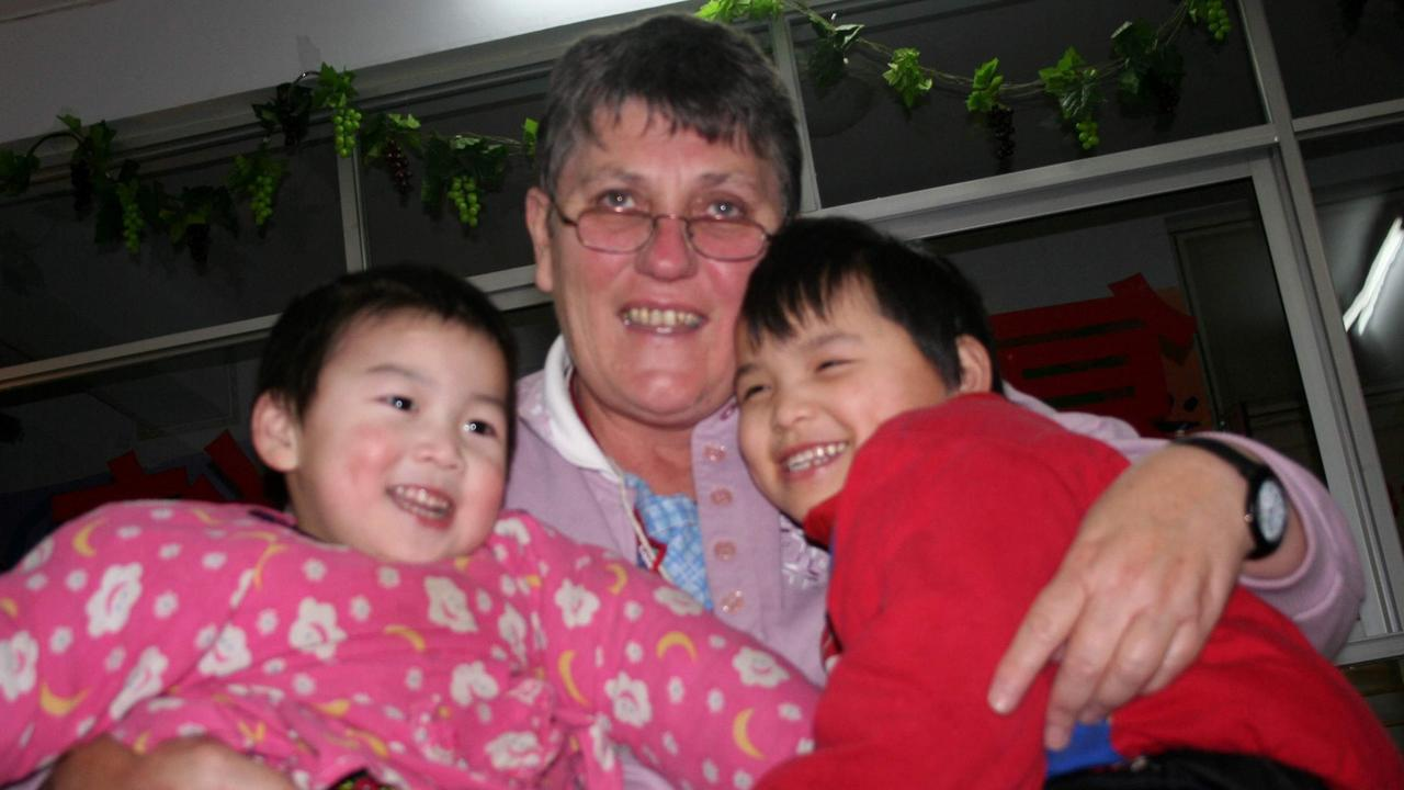 Linda Shum with two of the orphans under the care of the Gympie-based Chinese Orphans Assistance Team in China.