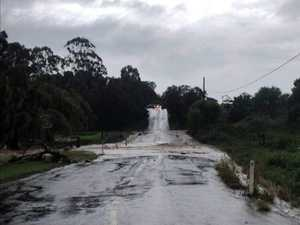 More than 100mm falls as rain cuts off roads