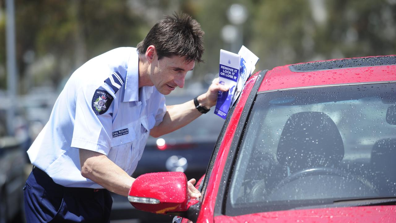 N23bm406 Locked Cars.  Ldg Sen-Constable Craig McDonald with cars at Watergardens Shopping Centre promoting car locking.