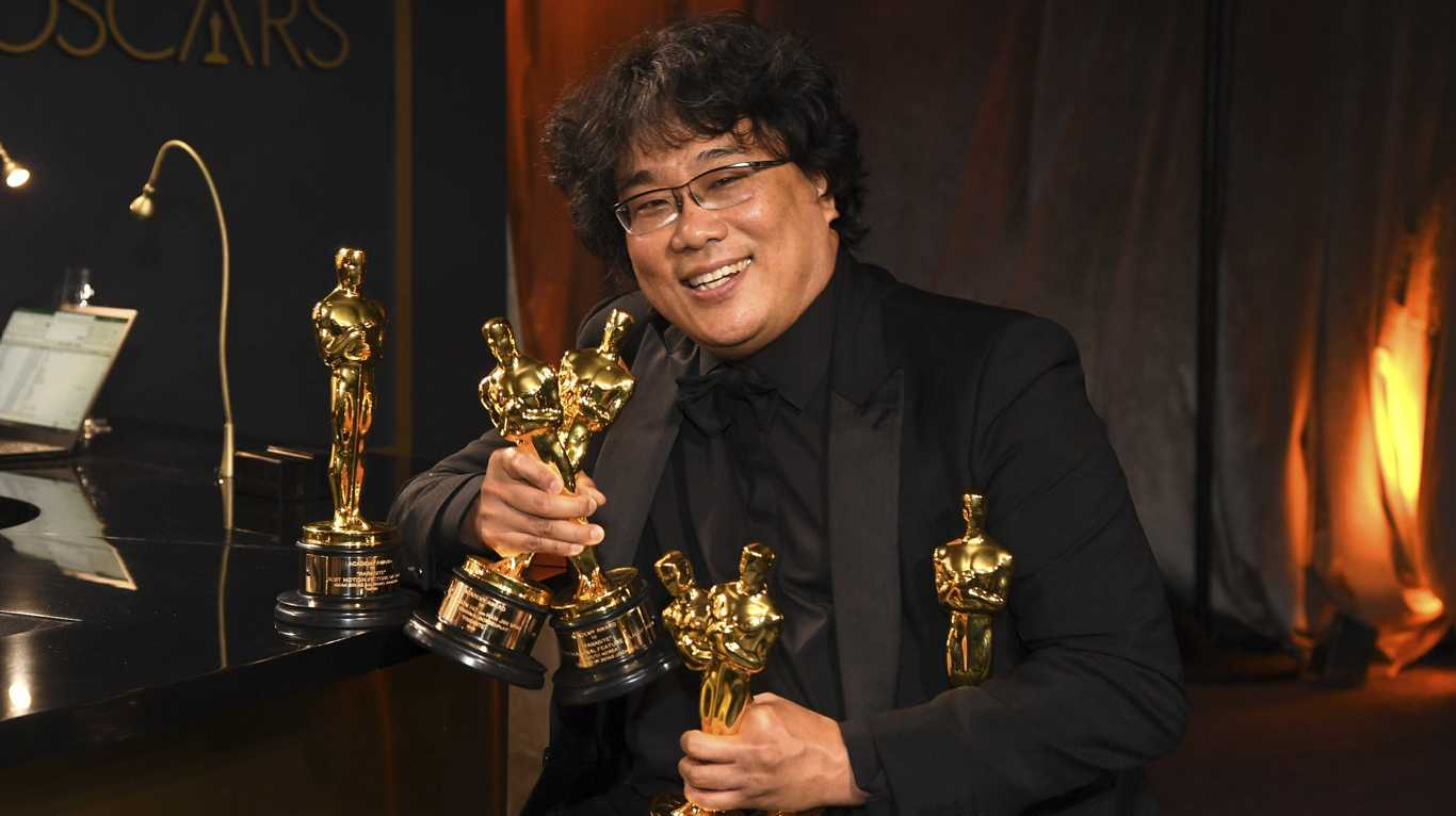 Bong Joon-ho holds the Oscars for best original screenplay, best international feature film, best directing, and best picture for Parasite at the Governors Ball after the Oscars at the Dolby Theatre in Los Angeles.