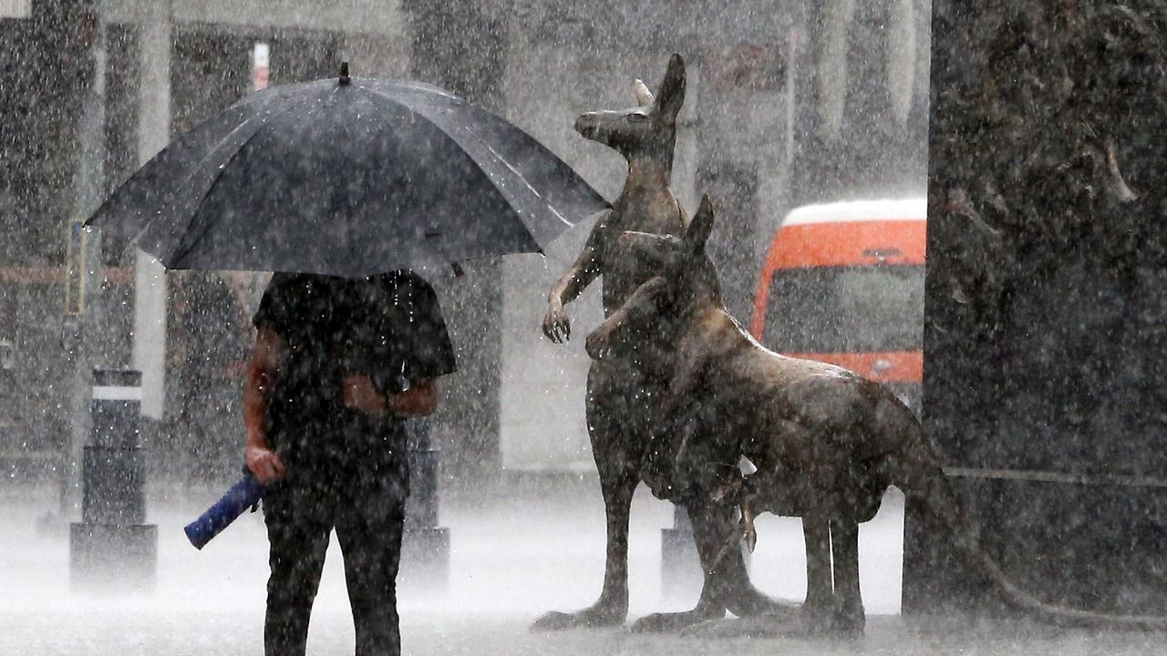 Heavy rain in Brisbane's CBD on Sunday morning. Picture: AAP/Richard Gosling