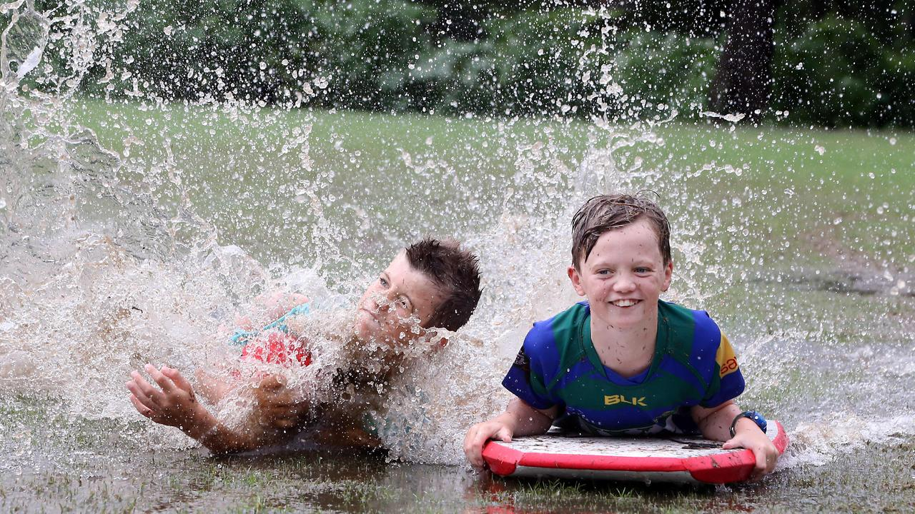 Finn McGahan and Matthew Travers having fun in the wet at Ashgrove. Picture: AAP/Richard Gosling