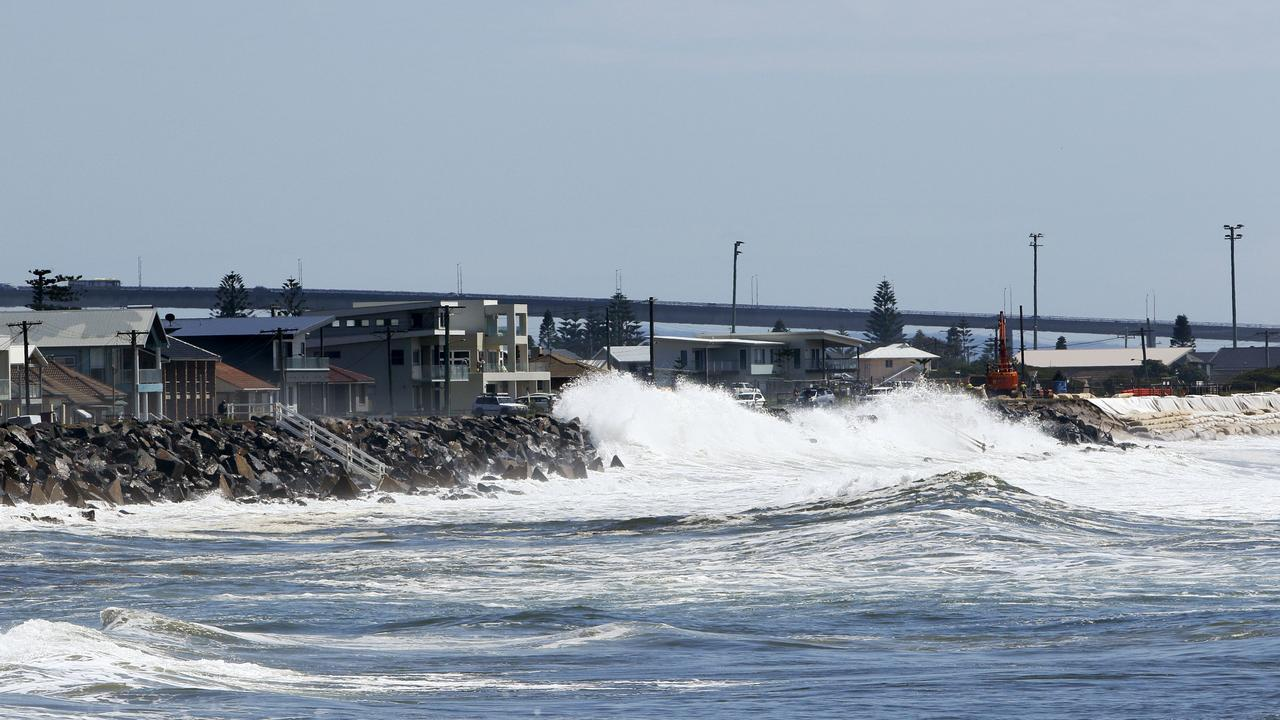 Newcastle City Council try to repair the sea wall (right) as erosion from large swell threatens to undermine them into the sea at Stockton Beach. Picture: AAP Image/Darren Pateman