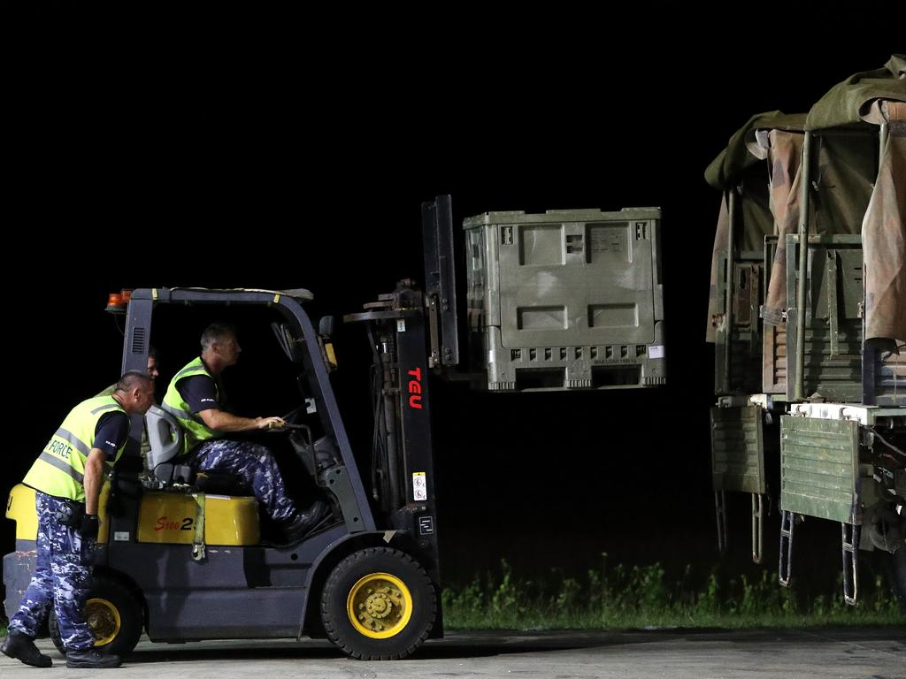 Australian military personnel load food and supplies onto trucks flown in from Darwin by a Hercules aircraft to Christmas Island. Picture: AAP