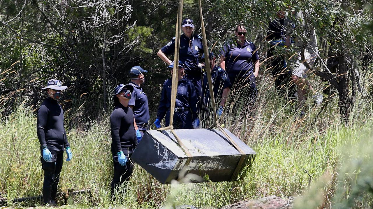 Police retrieve a metal box from a dam near Kingston. Picture: Jono Searle