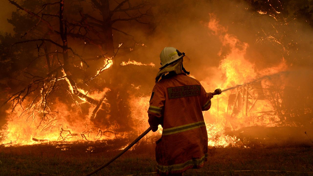 A firefighter tried to keep the flames at bay during the height of the blazes. Picture: Jeremy Piper