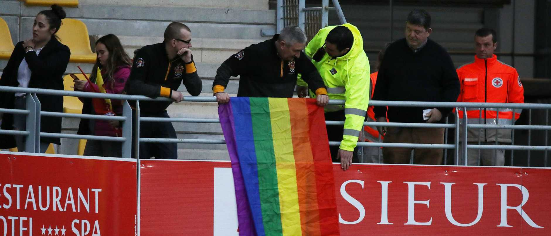 Two fans protesting Israel Folau's anti-gay statements at his first match of rugby league in a decade were asked by security to take down their rainbow flag.