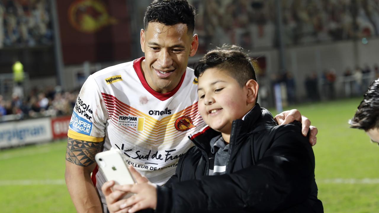 Catalans Dragons Israel Folau has his photo taken with a young fan after the Super League rugby match. Picture: AP Photo/Joan Monfort