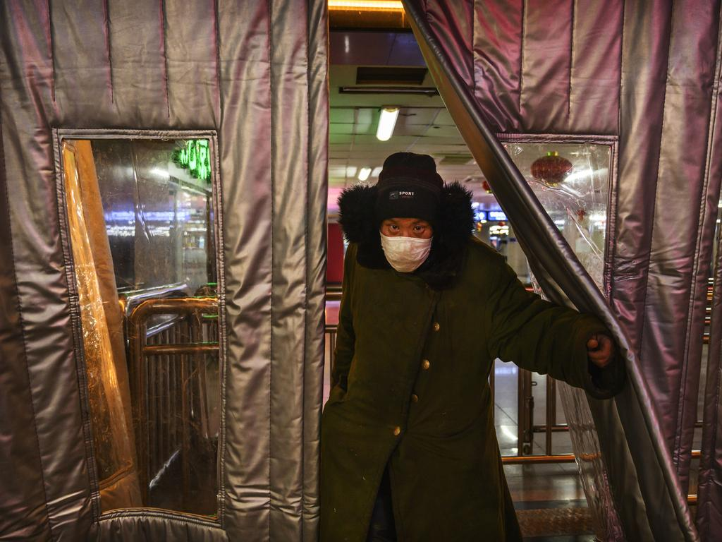 A Chinese man wears a protective mask as he walks outside of a subway station. Picture: Getty