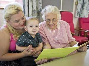 Nancy Hart reads to baby Alistair Leggett and his mum