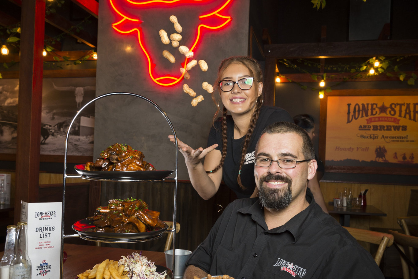 Taylor Trost and Lone Star Rib House Queensland manager Jy Diamond with the Sheriff's Rib Tower for two at the newly opened restaurant in Grand Central, Tuesday, February 18, 2020. Picture: Kevin Farmer