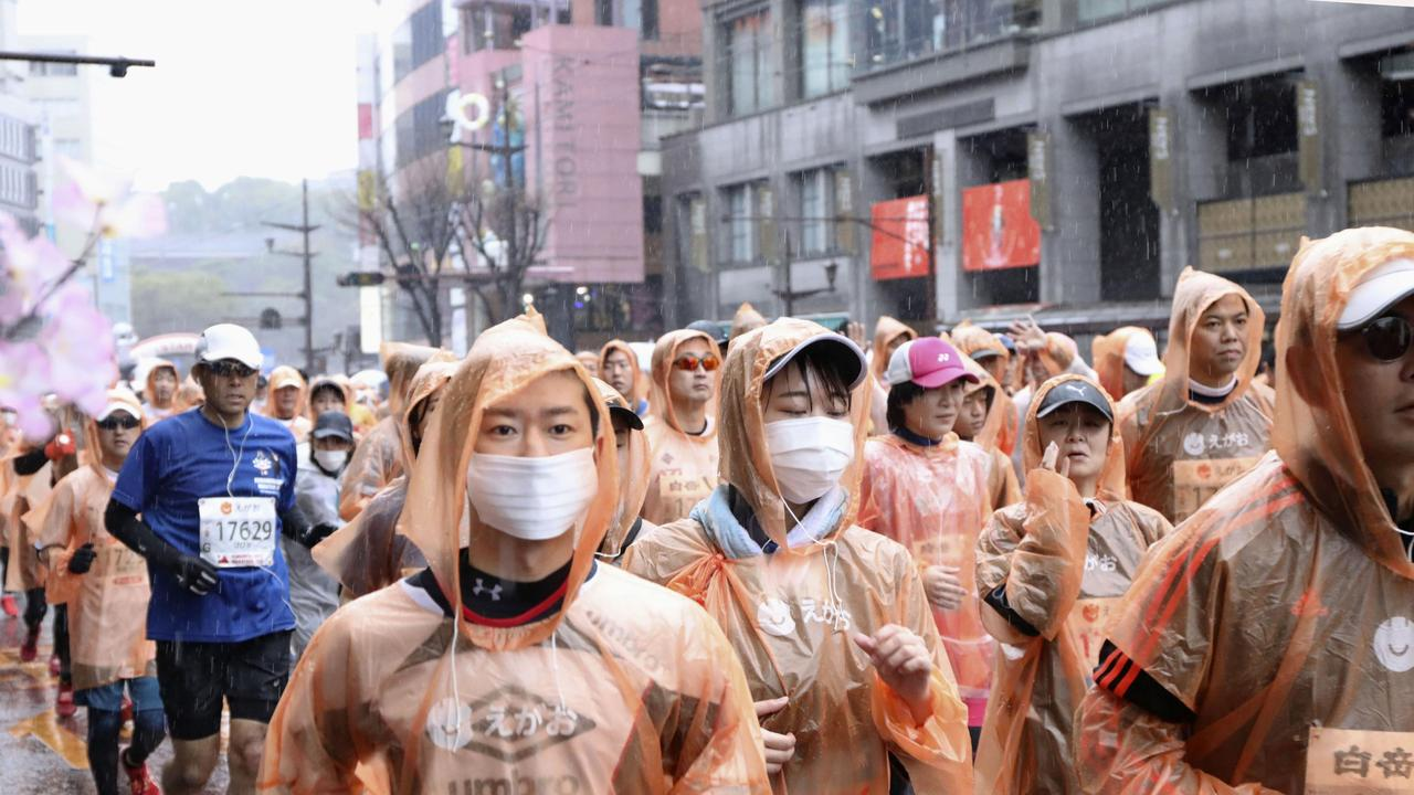 Runners wearing masks compete in a Kumamoto castle marathon in Kumamoto city, western Japan. Picture: Kyodo News via AP