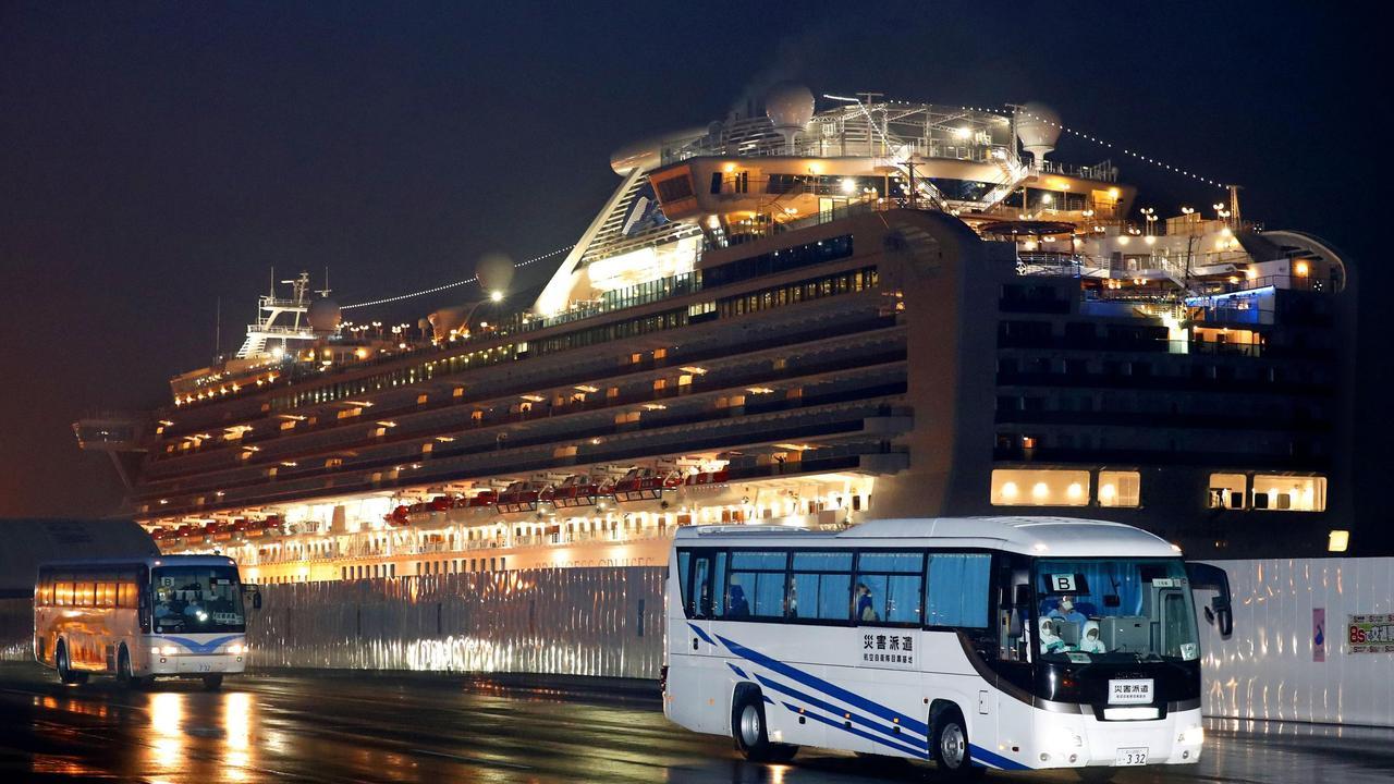 Buses carrying US passengers who were aboard the quarantined cruise ship the Diamond Princess, seen in background, leaves Yokohama port, near Tokyo, on February 17, 2020. Picture: Jun Hirata/Kyodo News via AP