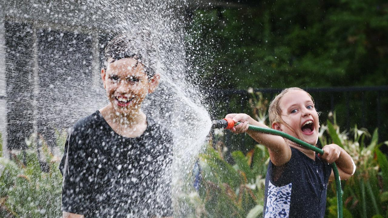 Stella Sattler, 8, and her brother Scott, 10, cool off from the heatwave conditions that the hot, sunny weather has brought to Cairns by spraying water from the garden hose over themselves at Redlynch. PICTURE: BRENDAN RADKE