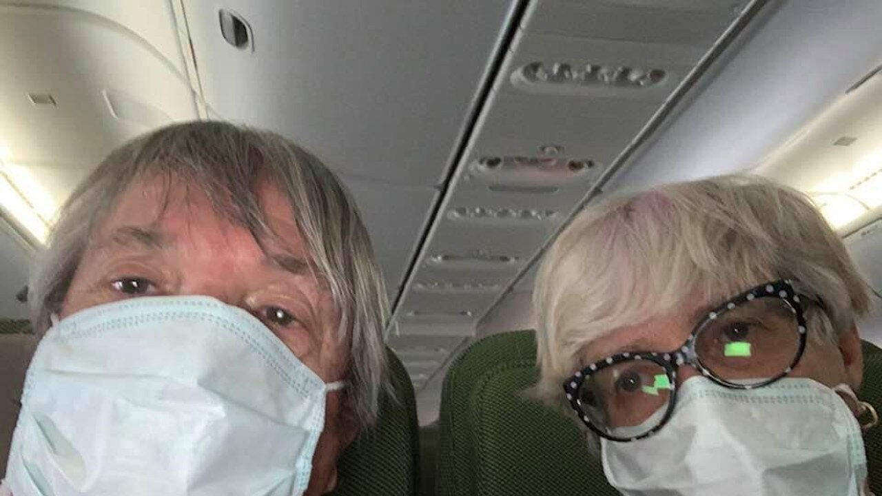 FLYING HOME: Dave and Jan Binskin on the flight from Japan to Australia to be quarantined for another two weeks at Howard Springs mining compound in Darwin. PIC: CONTRIBUTED