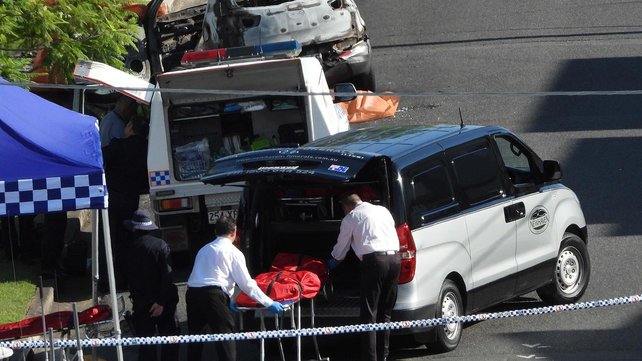 Police remove a body from a car after a man allegedly poured petrol on a woman and three children in Brisbane. Lyndon Mechielsen/The Australian