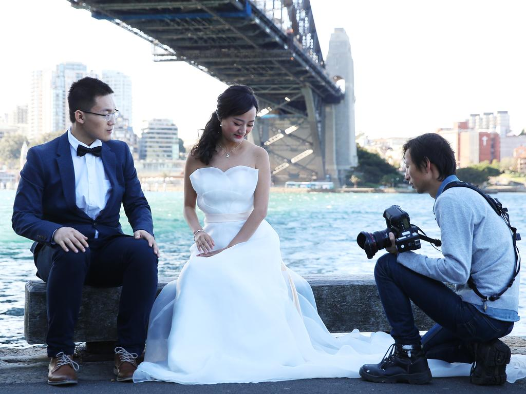 Chinese couple Eric Lei and Crystal Men get their wedding photos taken on Sydney Harbour by photographer Li Jiang. Australia has become a popular spot for Chinese honeymooners. Picture: Sam Ruttyn