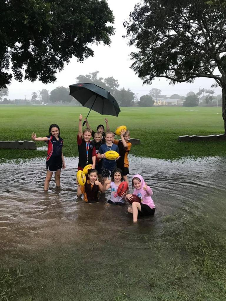 Sarina Demons junior AFL club members stand at the flooding fields during a downpour. Picture: Contributed