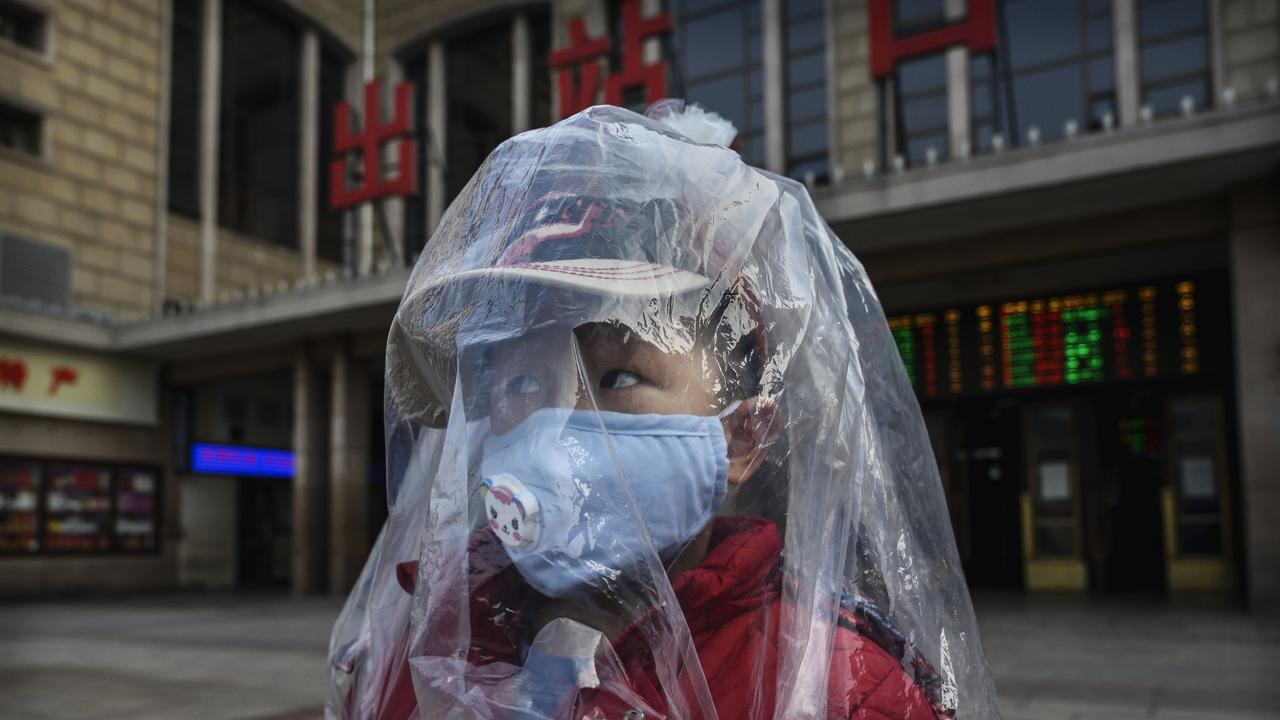 A Chinese boy is covered in a plastic bag for protection as he arrives from a train at Beijing Station. Picture: Kevin Frayer/Getty Images