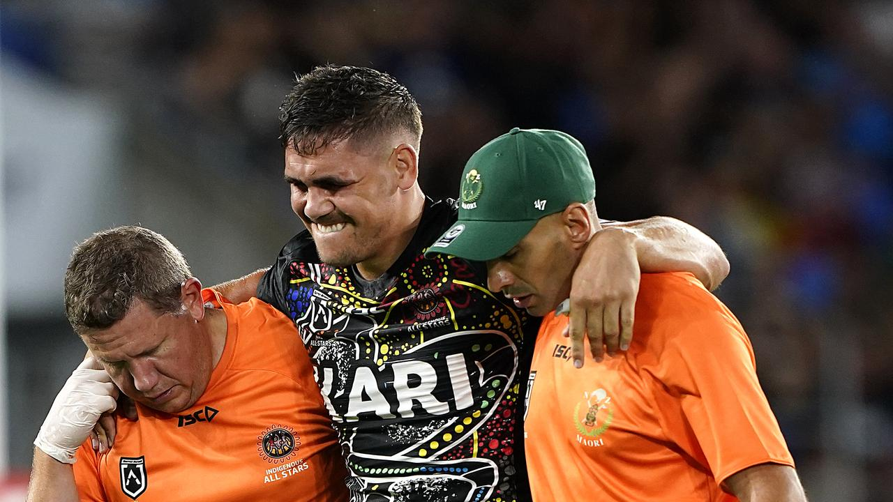 Chris Smith of the Indigenous All Stars is assisted from the field after sustaining ACL damage during the NRL Indigenous All-Stars vs Maori Kiwis match at Cbus Super Stadium on the Gold Coast, Saturday, February 22, 2020 (AAP Image/Dave Hunt) NO ARCHIVING, EDITORIAL USE ONLY