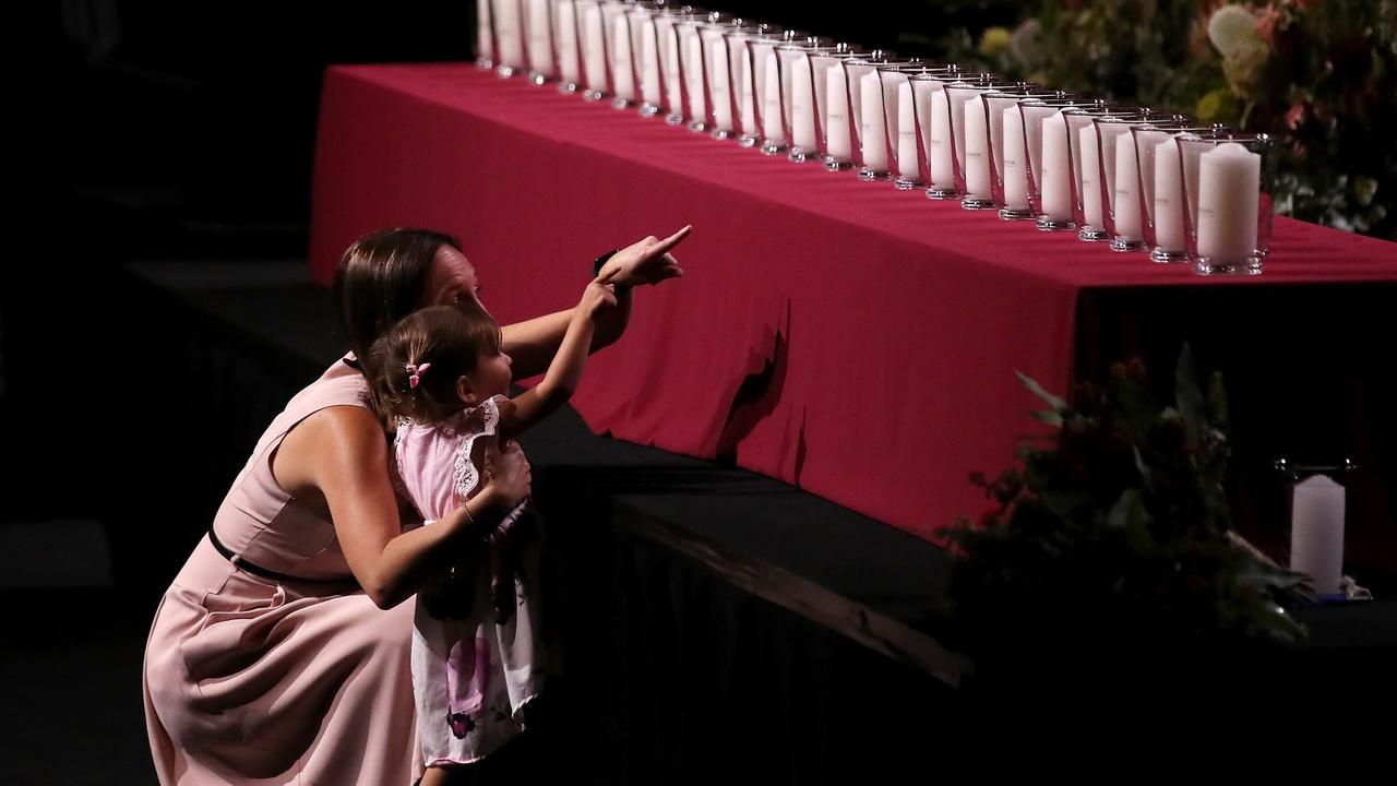Melissa O'Dwyer, widow of NSW firefighter Andrew O'Dwyer talks to her daughter Charlotte O'Dwyer while pointing out candles representing those who were deceased during a State Memorial Service. Picture: Cameron Spencer/Getty Images