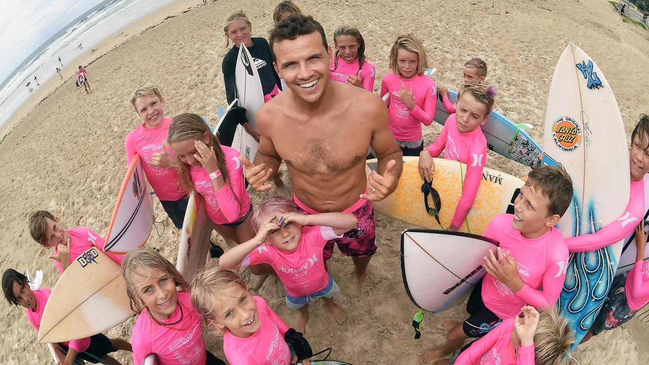 Junior surfers gather around their hero Julian Wilson at Coolum on Saturday for the Julian Wilson Serious Fun Invitational. Photo: Patrick Woods