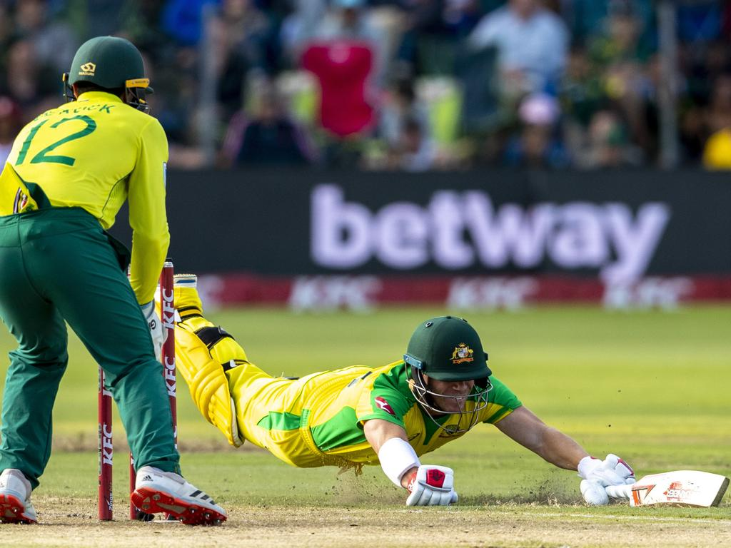 David Warner dives to survive a run out attempt by South Africa's captain Quinton de Kock. Picture: AP Photo/Themba Hadebe