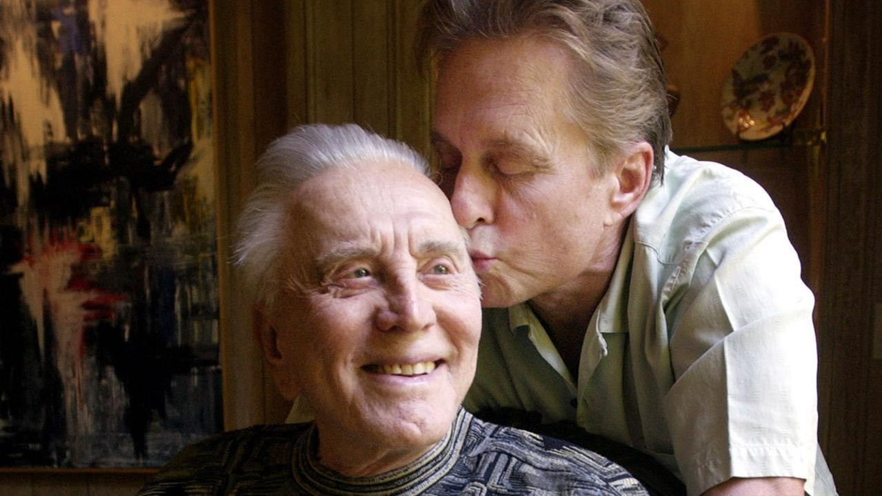 Michael Douglas kisses father Kirk in 2003. Picture: AP Photo/Chris Pizzello, File