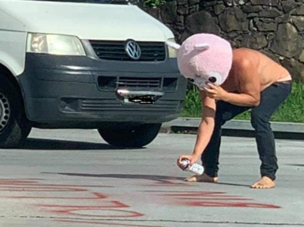 A man seen spray-painting graffiti onto a Byron Bay road.