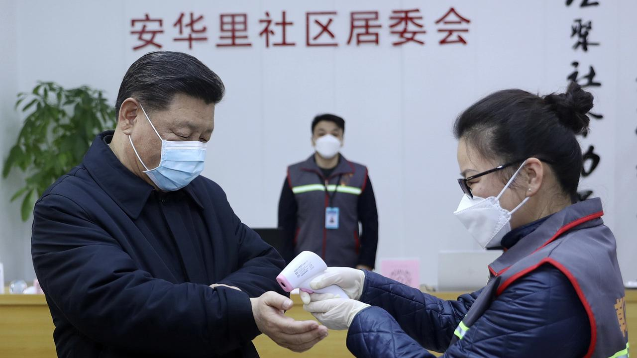 Chinese President Xi Jinping, left, wearing a protective face mask receives a temperature check as he inspects the coronavirus pneumonia prevention and control work at a neighbourhoods in Beijing. Picture: Pang Xinglei/Xinhua via AP