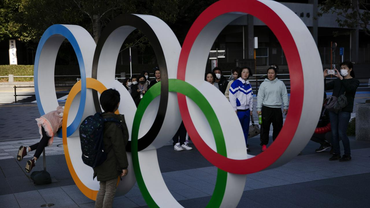 People wait in line to take pictures with the Olympic rings near the New National Stadium, Sunday, Feb. 23, 2020, in Tokyo. (AP Photo/Jae C. Hong)