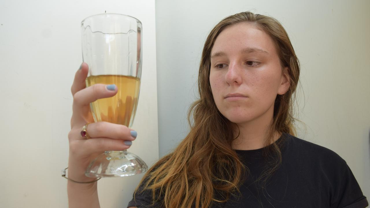 Resident Jess Walsh holding a glass of the discoloured water Clermont residents have had to endure for weeks. Photo: Zizi Averill