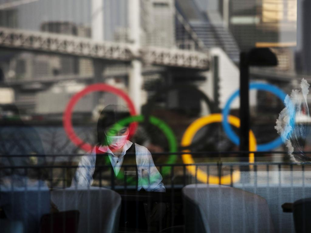 The Olympic rings are reflected in the window of a hotel restaurant as a worker with a mask sets up a table in the Odaiba section of Tokyo. Picture: AP