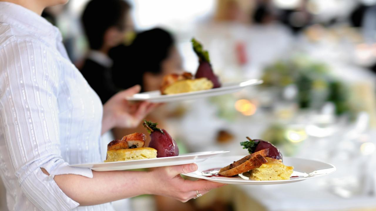New wage rules come into effect on Sunday from the Fair Work Commission for salaried staff working in restaurants, cafes and bar carrying three plates with meat dish.