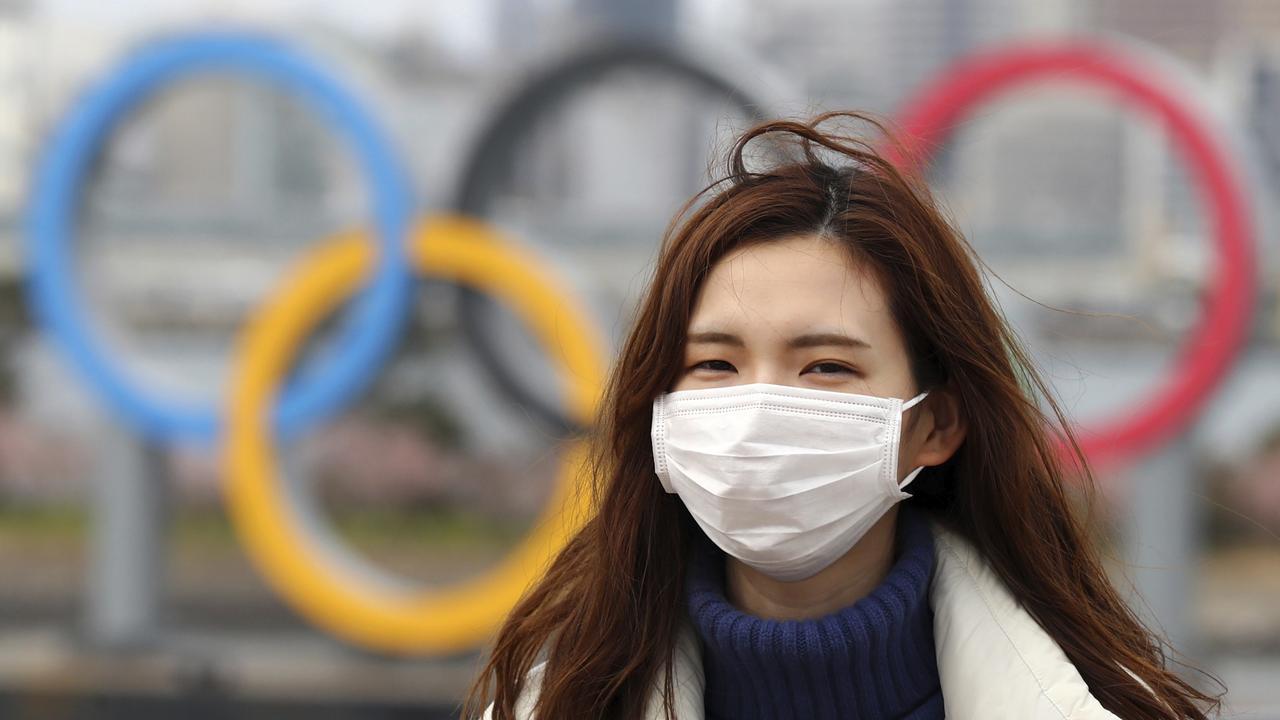 A woman wearing a mask walks near the Olympics' mark in Odaiba, Tokyo on February 22, 2020, amid the outbreak of a new coronavirus in Japan. ( The Yomiuri Shimbun via AP Images )
