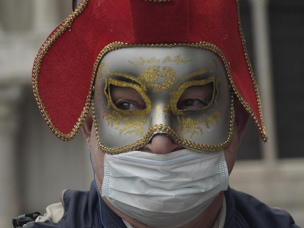 A Russian tourist dons both a carnival mask and a protective face mask as he visits St. Mark's square Venice. Picture: Photo/Renata Brito.