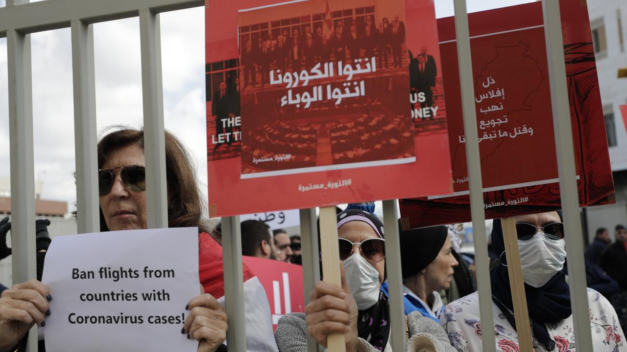 Anti-government protesters hold up banners in Arabic that read, 'You are the coronavirus, you are the epidemic, and Humiliation, bankruptcy, looting, starving and killing the rest of us' during ongoing protests against the Lebanese government in front of the Lebanese Ministry of Health, in Beirut, Lebanon. Picture: AP/Hassan Ammar.