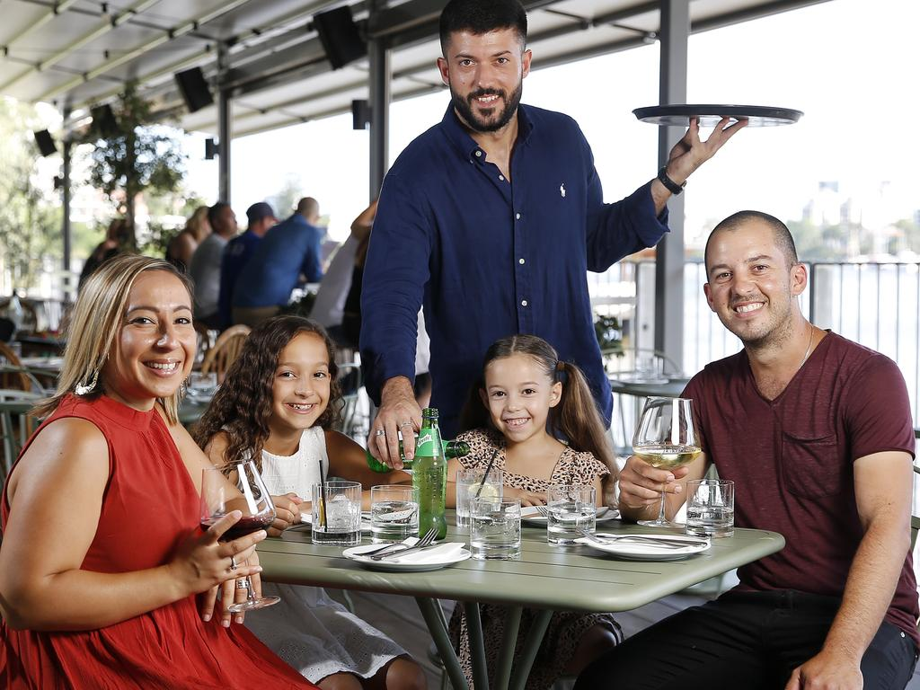 Cristal, Andrea, 10, Sophia, 8, and Chris Fysentzou with waiter Tom Torchut posing at Ciao Papi, Howard Smith Wharves, Brisbane. Picture: AAP