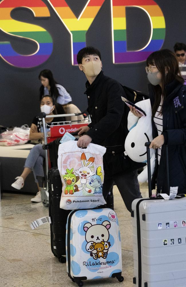 Coronavirus Arrivals Tourists arrive at Sydney International Airport wearing face masks. Picture: Brendan Read.