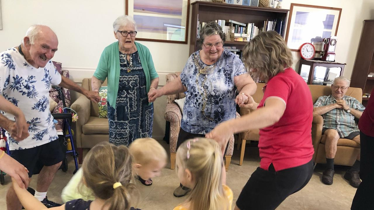Residents and pre-schoolers dance together as Cubby House for Kids visited Mareeba residents.