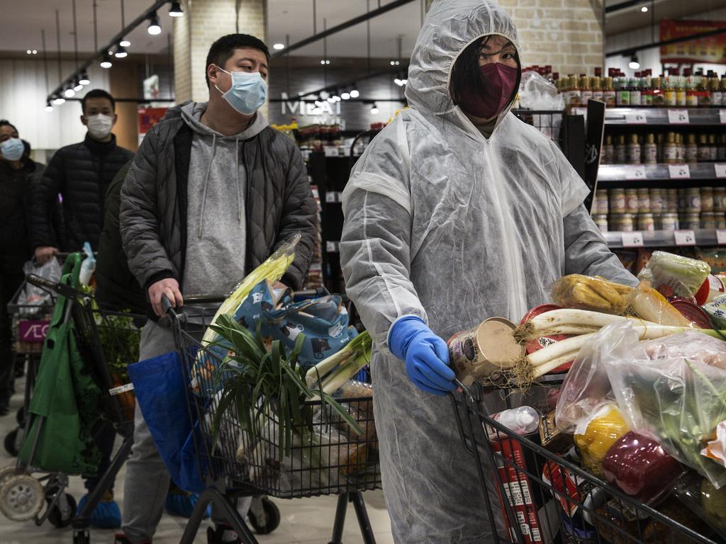 Residents wear protective masks as they line up in the supermarket in Wuhan. Picture: Stringer/Getty Images)