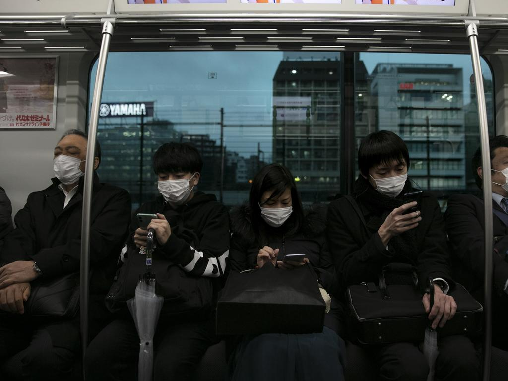 Commuters on a train in Tokyo wearing masks. Picture: AP