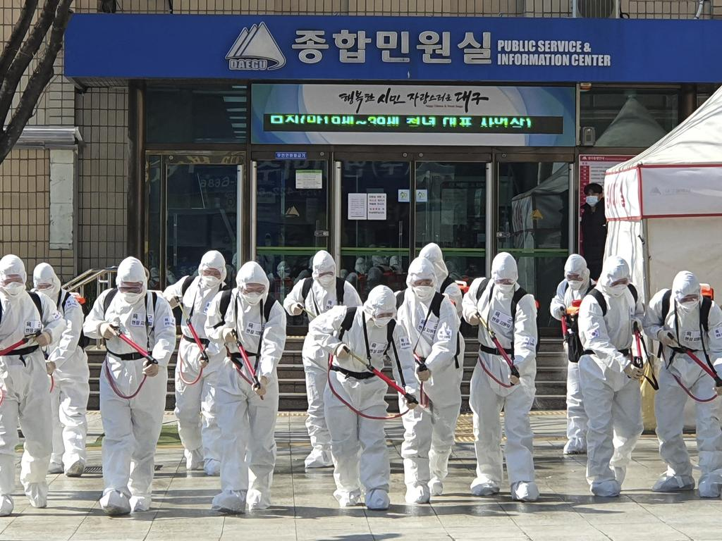 South Korean soldiers wearing protective suits spray disinfectant to prevent the spread of coronavirus in front of the Daegu city hall in Daegu, South Korea. Picture: AP
