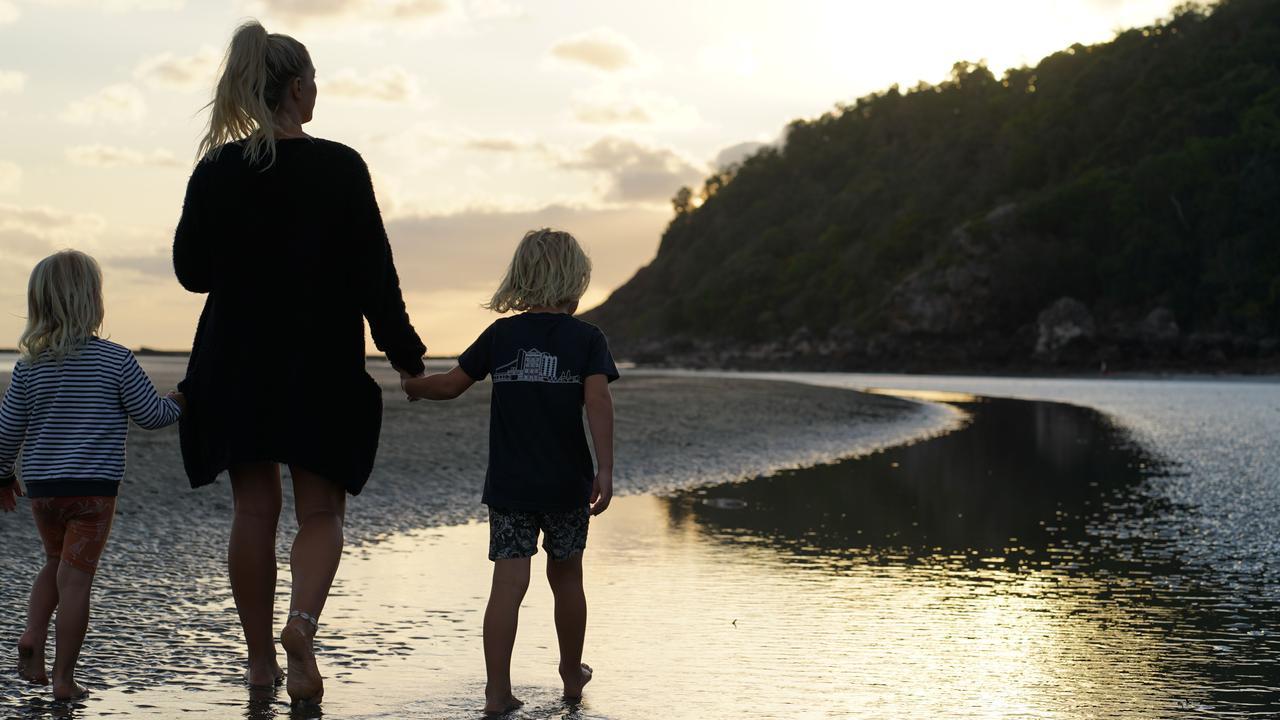 Bec Lorrimer with her children Charli Lorrimer, 4, left, and Billy Lorrimer, 6, walking along the beach at Cape Hillsborough.