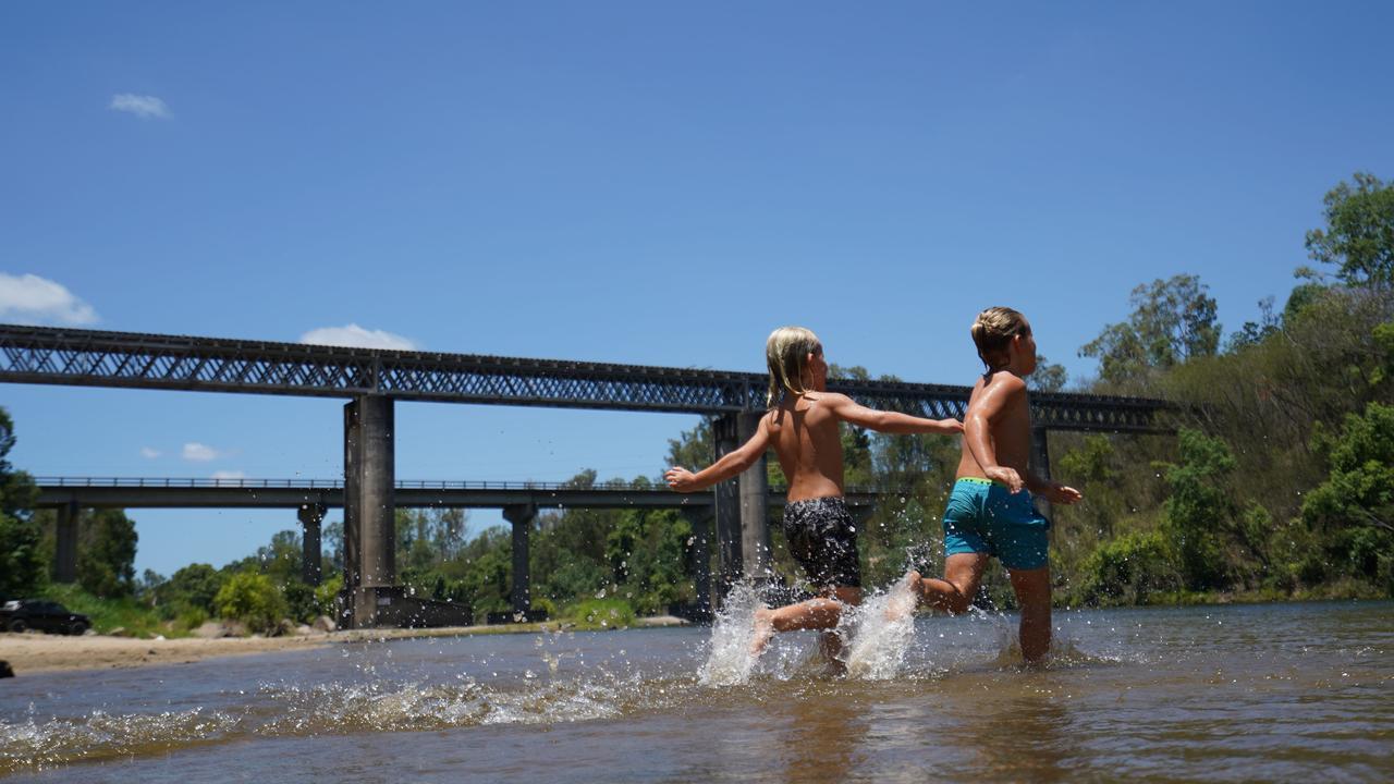 Jack Lorrimer, 7, and Billy Lorrimer, 6, running through the water at Mirani's Platypus Beach.